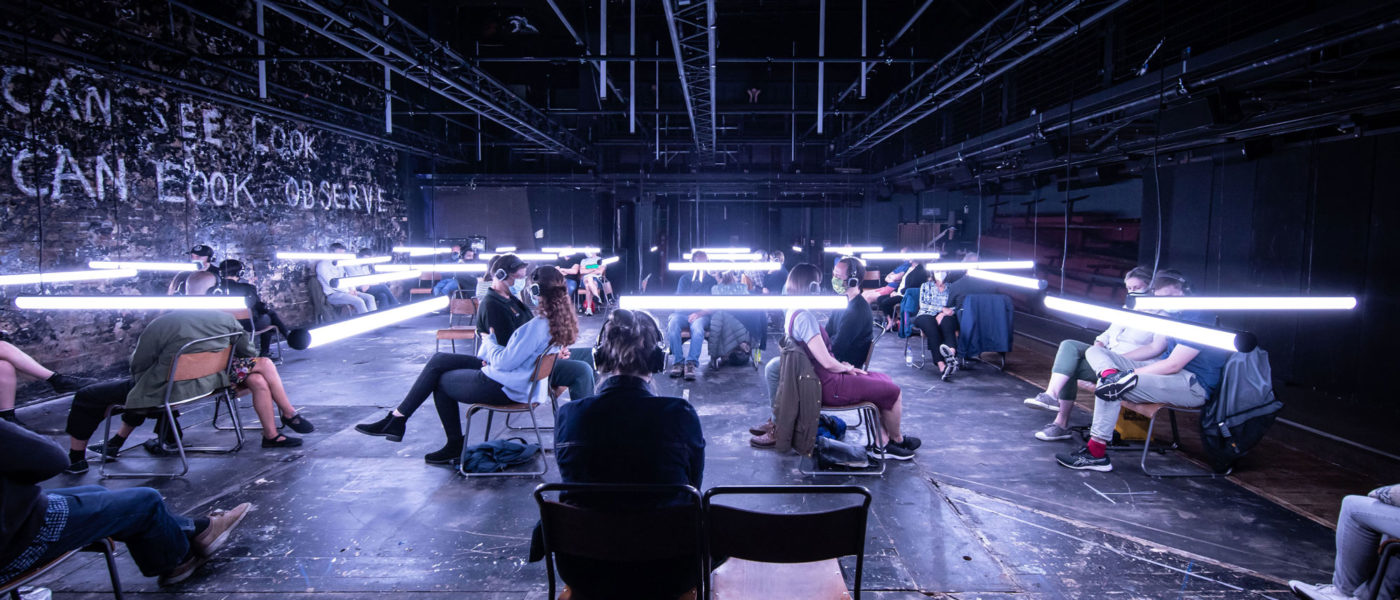 Visitors to Blindness sit on wooden chairs, arranged 2 metres apart around the Donmar auditorium, wearing headphones. A grid of lights hangs at eye level to the visitors, illuminating the space with a bright white light.